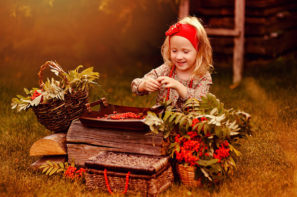 happy child girl making rowan berry beads in sunny autumn garden